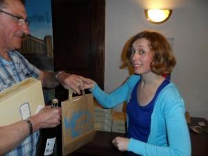 remise d'une pochette avec divers prospectus sur le Cotentin par l'organisatrice de séjour dans la région; d'une boîte de gâteaux (financiers) et d'une bouteille de cidre du pays le tout offert avec le sourire (Louison tu lui fais mal!)